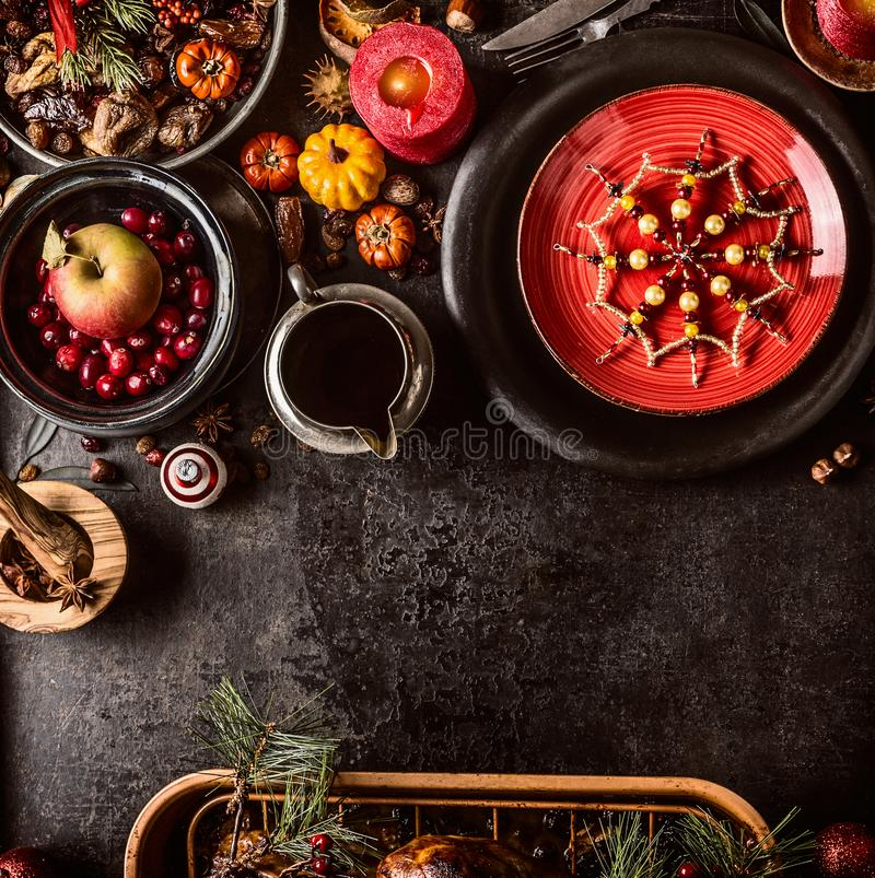 Christmas dinner background with festive table setting, snowflakes decoration, sauce, fresh cranberries and apple, pumpkins, nuts royalty free stock photography