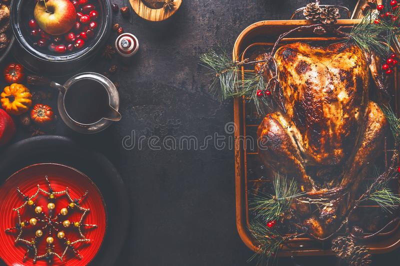 Christmas dinner background. Roasted stuffed turkey served with fresh cranberries, pine branches and sauce on rustic background. With red plate, snowflakes royalty free stock image