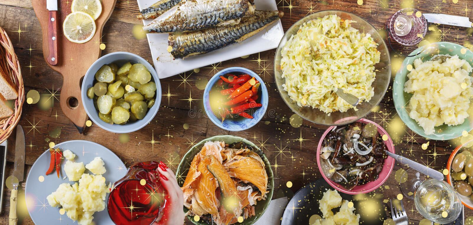Christmas dinner with family. Traditional snacks and wine. Falling golden snowflakes. Top veiw royalty free stock photography