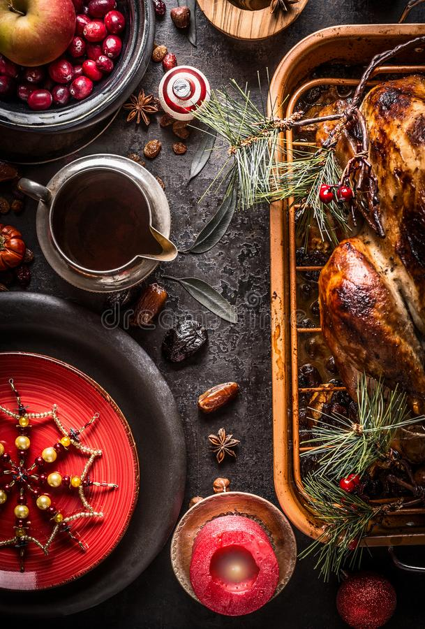 Christmas dinner. Festive table setting with roasted turkey served with pine branches and sauce on rustic background with burning. Candles, red plate stock image