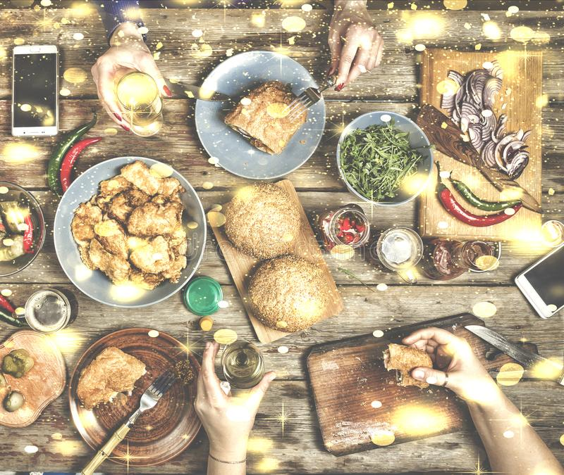 Christmas dinner with friends. Traditional American snacks, burgers, Chicken nuggets with Christmas wine or crafted beer, top view. Falling snow, golden stock photos