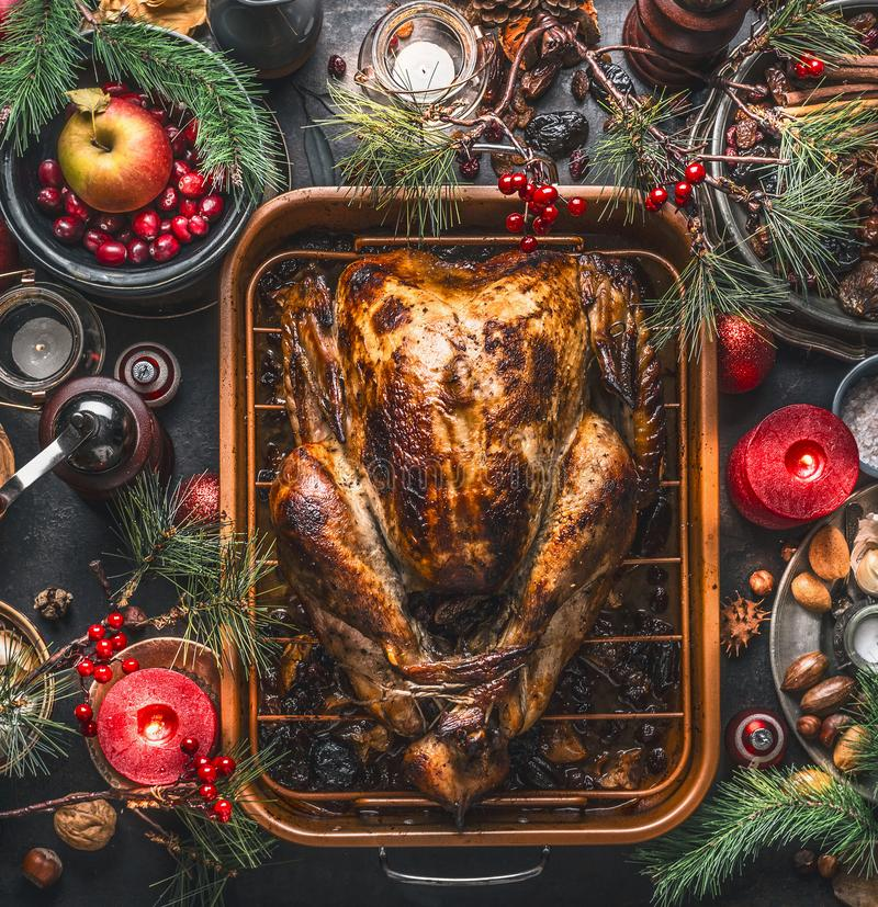 Christmas dinner. Roasted stuffed turkey served with fresh cranberries, pine branches on rustic background with burning candles,. Nuts, apple and little stock photography