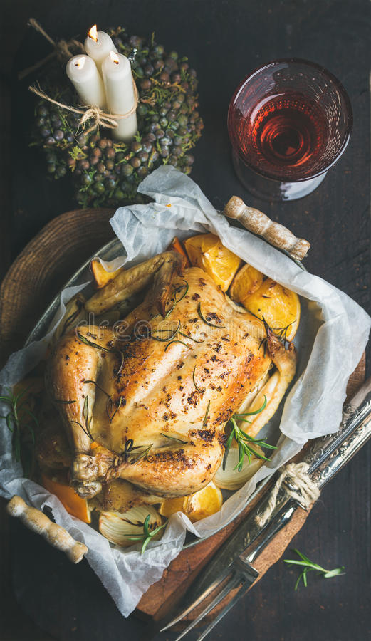 Christmas dinner with roasted whole chicken, decorative candles and wine. Christmas holiday table set with oven roasted whole chicken stuffed with oranges royalty free stock photos
