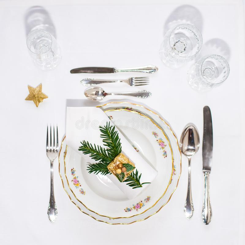 Christmas dinner set: porcelain plates, silver cutery and white. Napking lying via diagonal line with christmas decoration. Flatlay. Copy space royalty free stock image