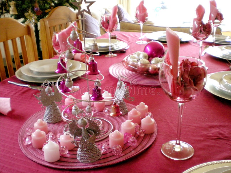 Christmas dinner table. A colorful laid table decorated different in pink with xmas decoration for a christmas dinner in the dining-room indoors at home stock image