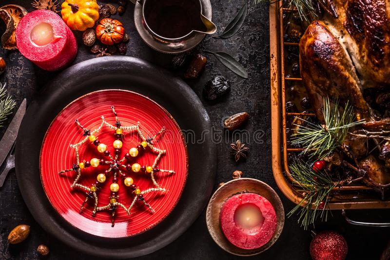 Christmas dinner table with red plate, snowflakes decoration, roasted turkey, pine branches and sauce on rustic background with. Burning candles, nuts and stock photography