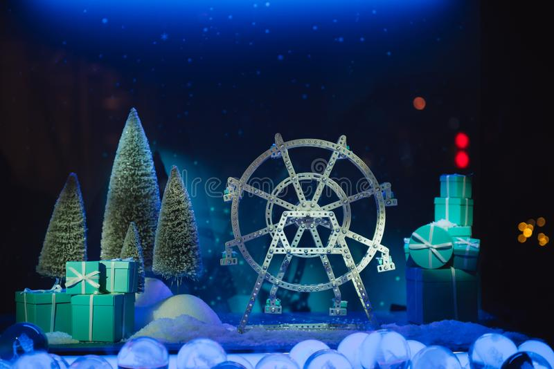 Christmas display decoration in dark blue tone. Christmas display decoration with ferris wheel, gift box, pine tree and snowball in dark blue light stock photography