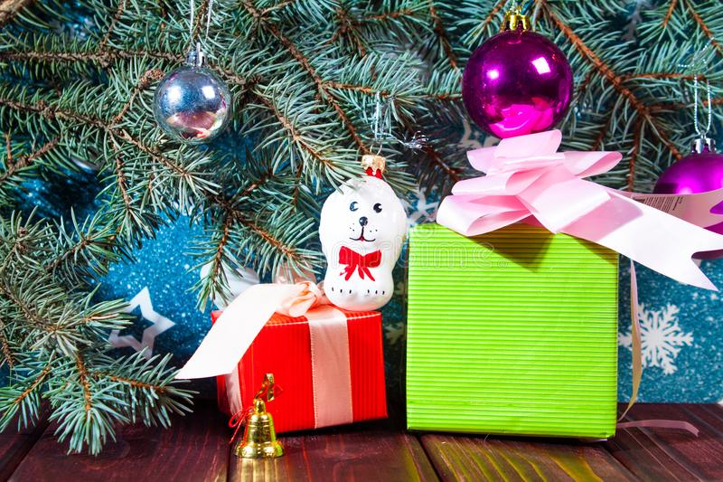 A toy dog in Santa hat and Christmas gifts on the background of coniferous branches. Christmas dog figurine background a toy dog in Santa hat and Christmas gifts royalty free stock photos