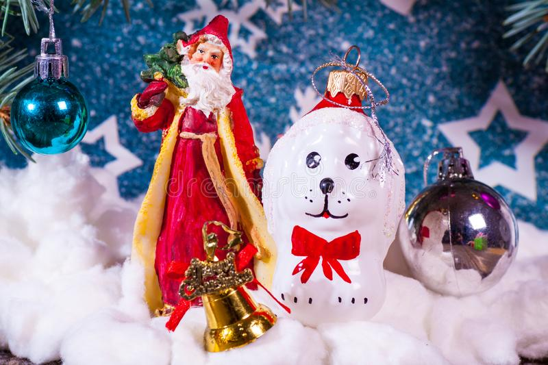 A toy dog in Santa hat and Christmas gifts on the background of coniferous branches. Christmas dog figurine background a toy dog in Santa hat and Christmas gifts royalty free stock image