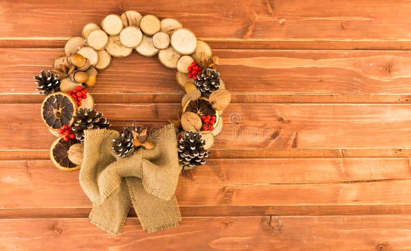 Christmas door decoration homemade of wood, jute and pinecones royalty free stock image