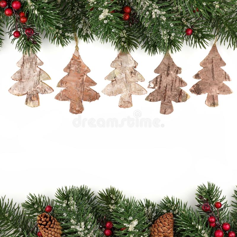 Christmas double border of branches with rustic wood tree ornaments over white royalty free stock photography