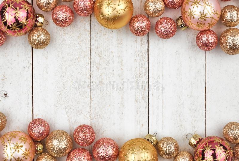 Christmas double border of rose gold and golden ornaments on white wood stock images