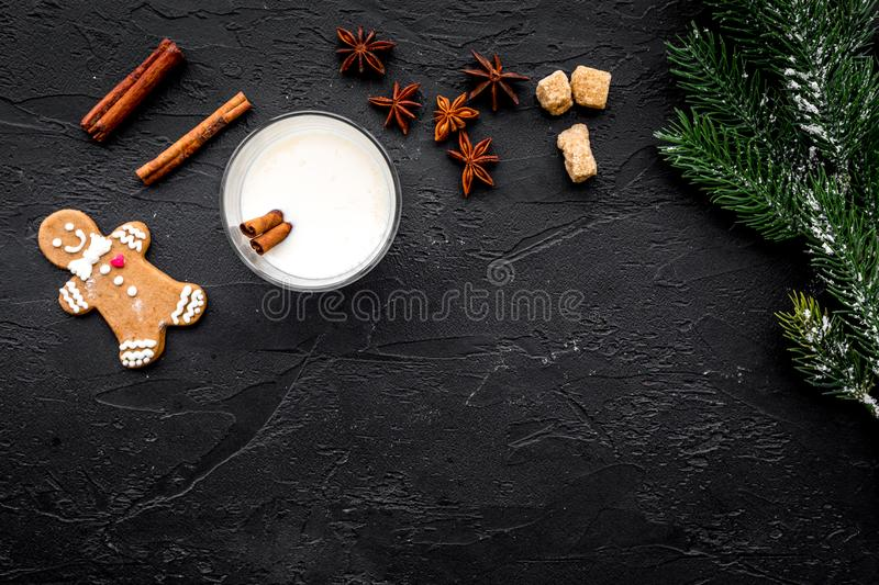Christmas drink cooking eggnog in glasses for celebration with cinnamon and spruce black table background flat lay mock. Christmas drink cooking eggnog in royalty free stock photos