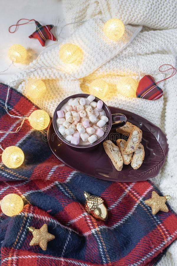 Christmas drink flat lay - hot chocolate with marshmallows, red and gold deco baubles, garland, knitted checkered plaid, hygge. Style royalty free stock images