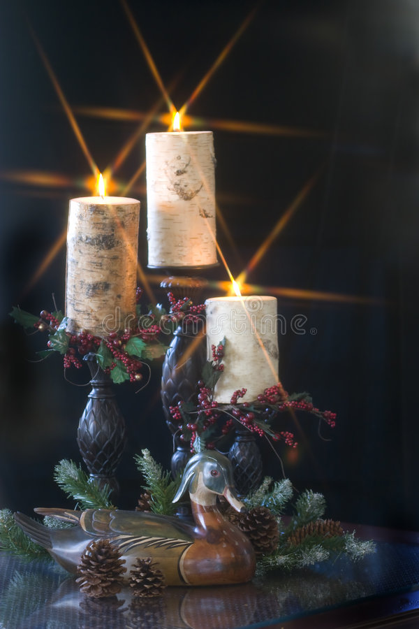 Christmas Duck with candles. Vintage handcrafted decoy wood duck with pine greenery and lighted candles royalty free stock photos