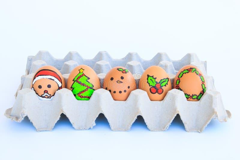 Christmas egg with faces drawn arranged in carton stock photos