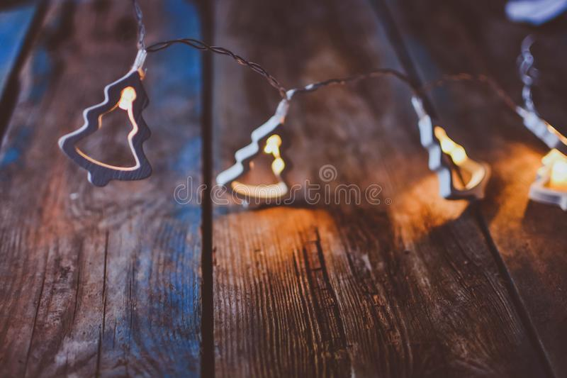Christmas electric garland on a wooden table. Rustic background royalty free stock photo