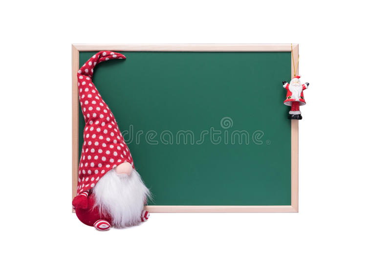 Christmas Elf and Santa Claus Ornament Beside an Empty Green Chalkboard on a White Background royalty free stock photos