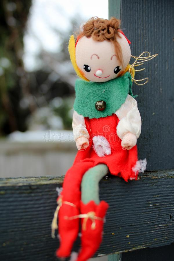 Christmas Elf on a Shelf Outdoors Sitting on wood fencing royalty free stock photo