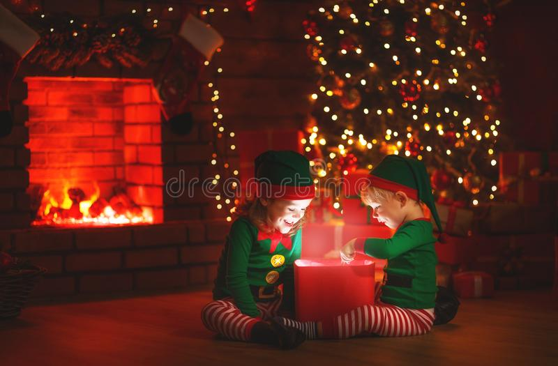 Christmas. elves with a magic gift near Christmas tree and fireplace. Christmas. elves with a magic gift near Christmas tree and a fireplace royalty free stock image