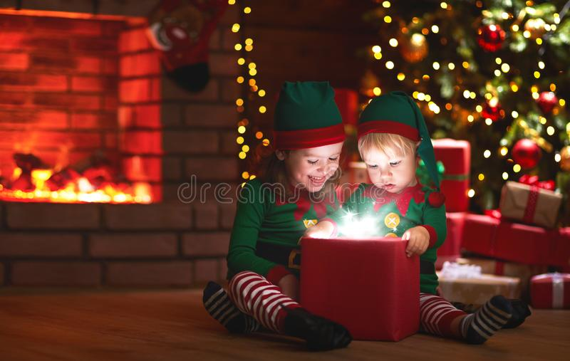 Christmas. elves with a magic gift near Christmas tree and fireplace. Christmas. elves with a magic gift near Christmas tree and a fireplace royalty free stock photo