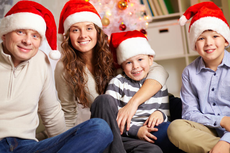 Christmas Eve. Portrait of four happy family members in Santa caps looking at camera at home royalty free stock photos