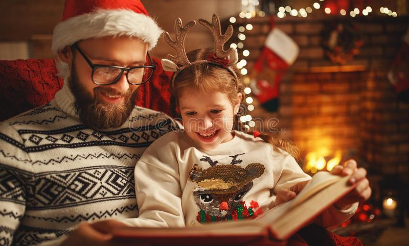 Christmas Eve. family father and child reading magic book at home. Near the fireplace and the Christmas tree royalty free stock photos