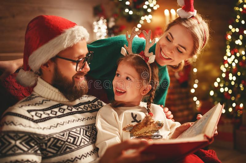 Christmas Eve. family father, mother and child reading magic book at home royalty free stock image