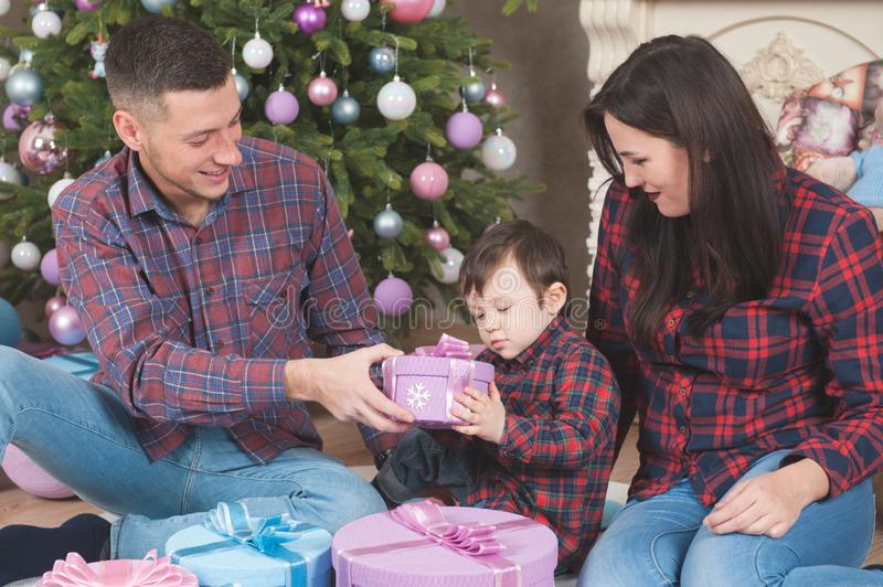 Christmas eve family holiday happy mother and father with little. Christmas eve family holiday happy caucasian mother and father with little baby open gift royalty free stock photography