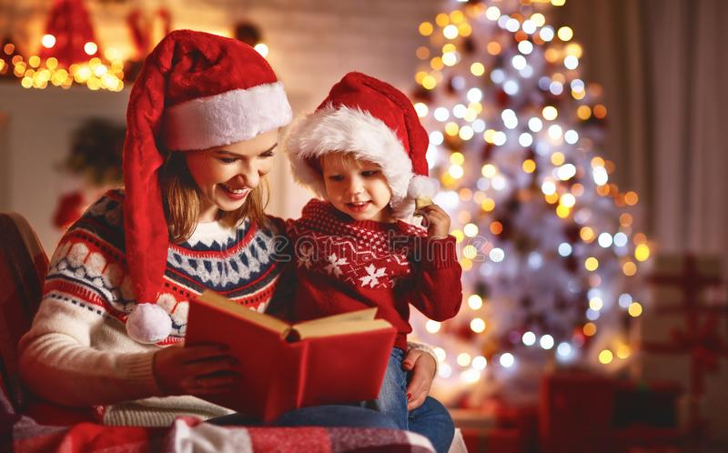 Christmas Eve. family mother and baby reading magic book at home. Near the fireplace and the Christmas tree royalty free stock photography