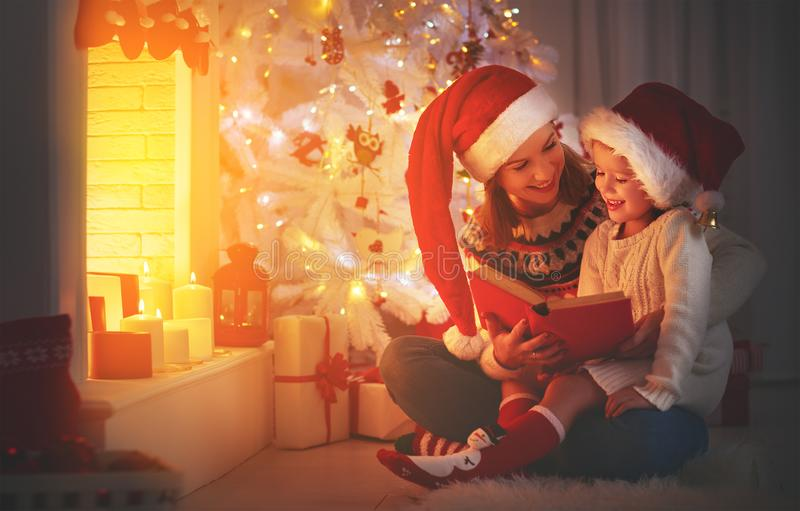 Christmas Eve. family mother and child daughter reading magic bo stock photography