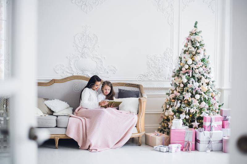 Christmas Eve. family mother and child daughter reading magic book at home on a sofa near Christmas tree.  royalty free stock photos