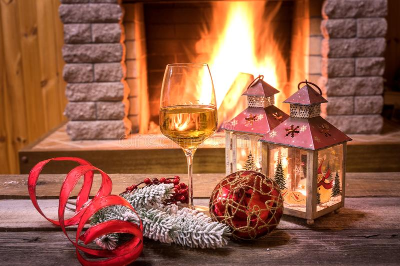 Christmas . Glass of wine and christmas lanterns near cozy fireplace, in country house. Christmas. Glass of wine, christmas lanterns and christmas decorations stock images