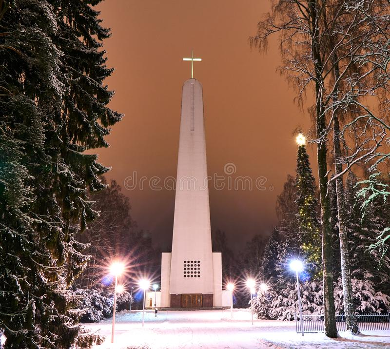 Christmas evening scenery at modern churchyard. Modern church at still snowy scenery in cold christmas night. Ground has snow cover. Christmas decorations at stock images
