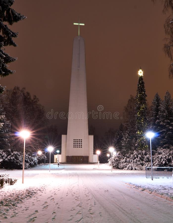 Christmas evening scenery at modern churchyard. Modern church at still snowy scenery in cold christmas night. Ground has snow cover. Christmas decorations at stock image