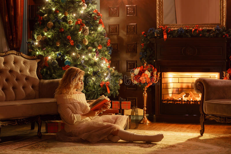 Christmas evening. Young beautiful blonde woman read book in classic apartments a fireplace, decorated tree. royalty free stock photography