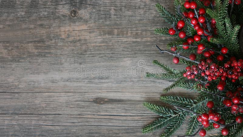 Christmas Evergreen Branches and Berries Over Rustic Wood Horizontal Background stock photo