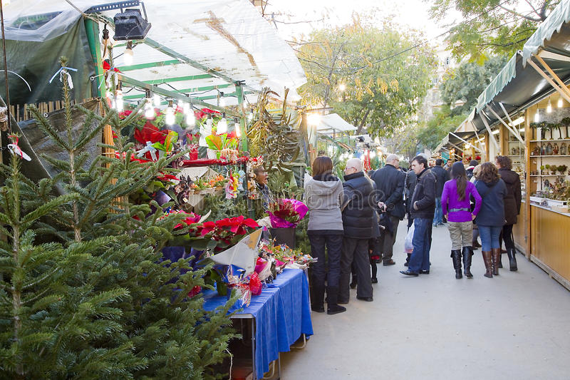 Christmas fair in Barcelona. People visit the famous Santa Llucia Fair near Sagrada Familia cathedral to buy Christmas decoration, as fir trees and crib figures stock photo