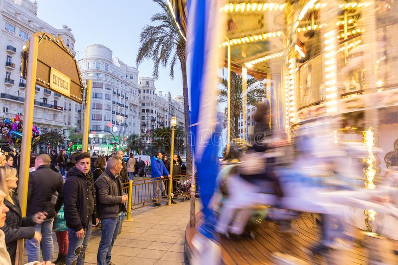 Christmas fair with carousel on Modernisme Plaza of the City Hall of Valencia, Spain. Valencia, Spain - Dec 16, 2017: People having fun in christmas spirit on stock image