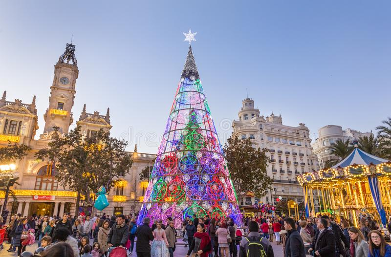 Christmas fair with colorful christmas tree and carousel on Modernisme Plaza of the City Hall of Valencia, Spain. Valencia, Spain - Dec 16, 2017: People having royalty free stock image
