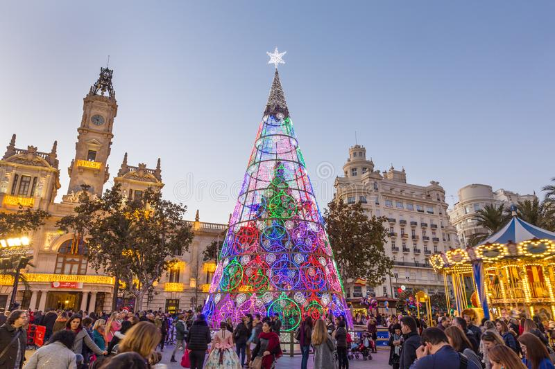 Christmas fair with colorful christmas tree and carousel on Modernisme Plaza of the City Hall of Valencia, Spain. Valencia, Spain - Dec 16, 2017: People having royalty free stock photos