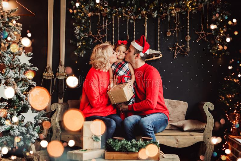 Christmas family with baby smiling and kissing near the Xmas tree. Living room decorated by Christmas tree and present gift box royalty free stock photos