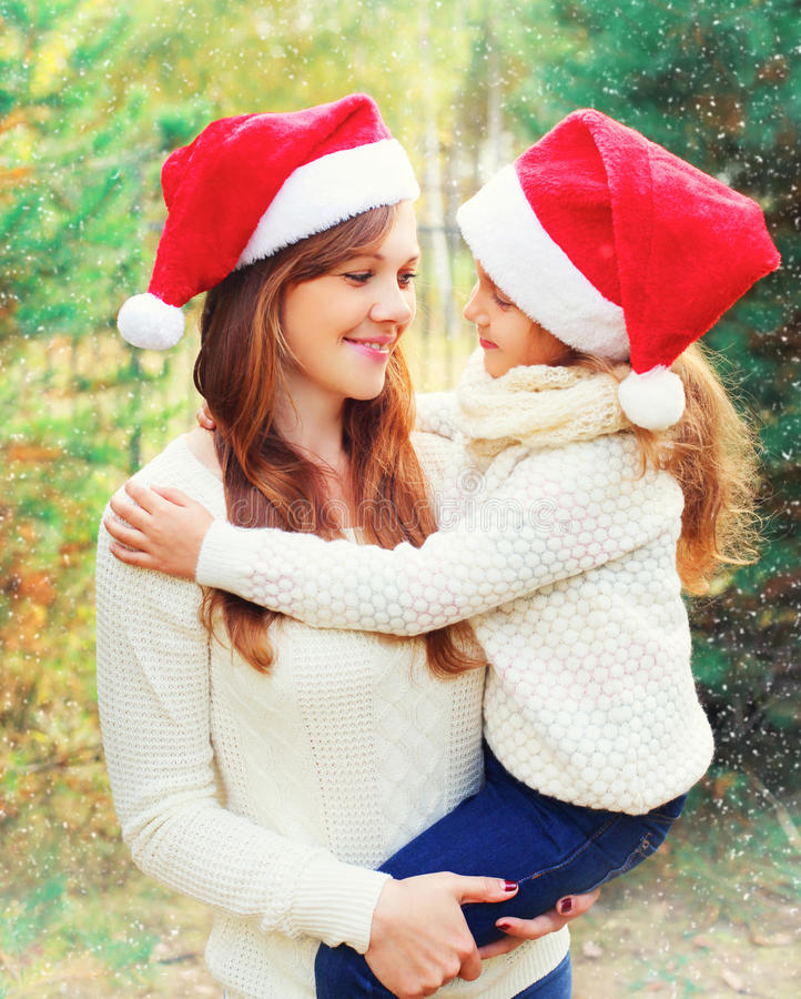 Christmas family, child hugging mother in santa red hats together over tree having fun royalty free stock image