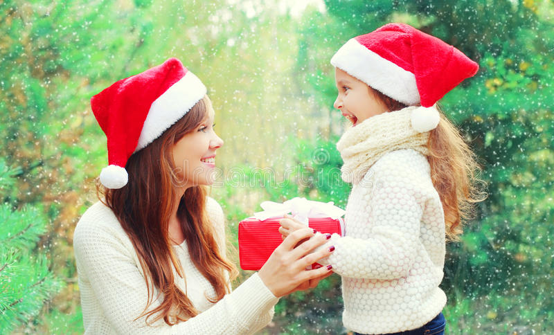 Christmas family child and mother in santa red hat with box gift over tree stock image