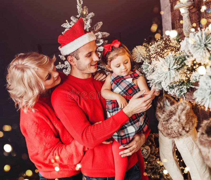 Christmas family with child smiling near the Xmas tree. Living room decorated by Christmas tree and present gift boxes, the ligh royalty free stock photos