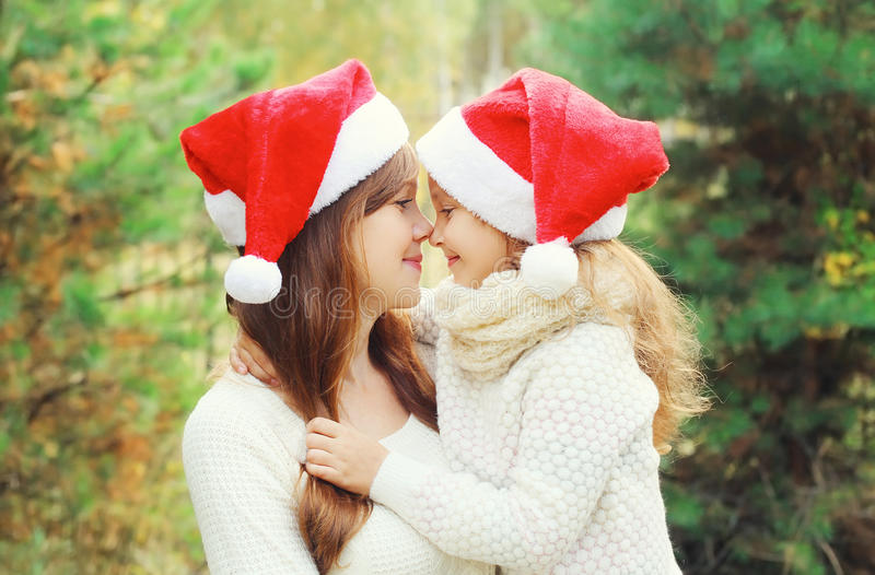 Christmas and family concept - child and mother in santa red hats. Together stock photo