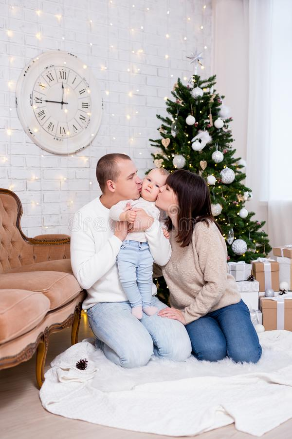 Christmas and family concept - happy young parents kissing cute little baby girl daughter near decorated christmas tree. Christmas and family concept - happy stock images