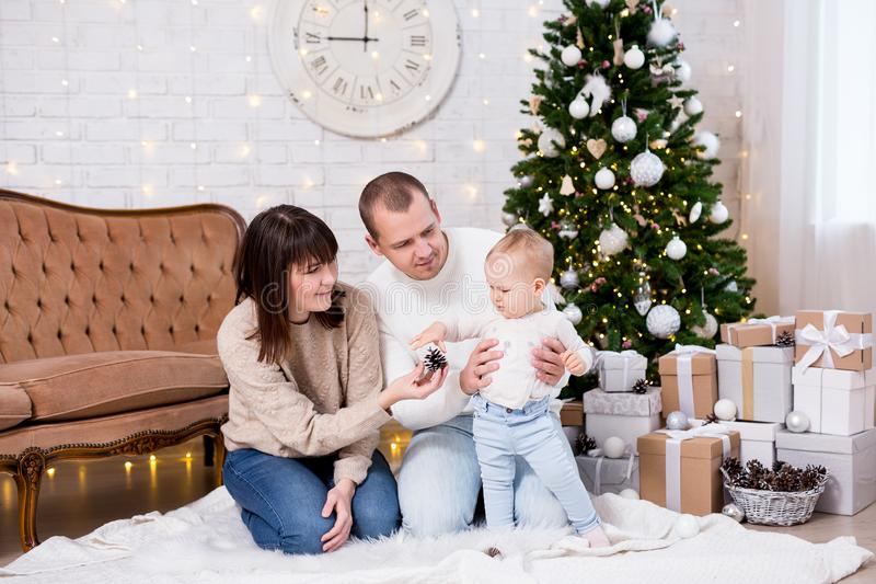 Christmas and family concept - happy young parents playing with cute little baby girl daughter near decorated christmas tree stock photo