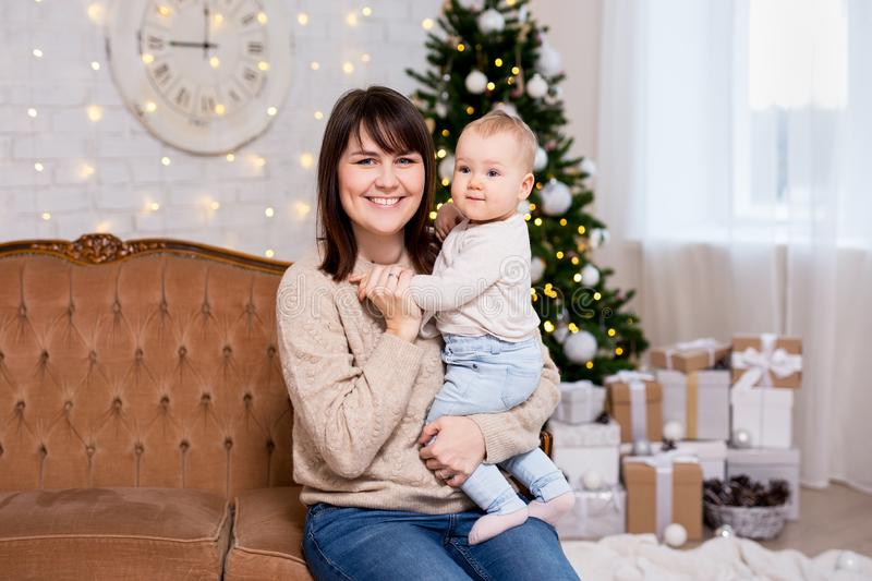 Christmas and family concept - mother and cute little baby girl daughter near decorated christmas tree royalty free stock photo
