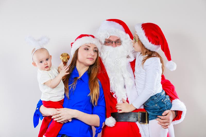 Mother, Santa and two daughters christmas family photo. Christmas family concept. Mother, toddler girl, baby, and men wearing Santa Claus costume stock image